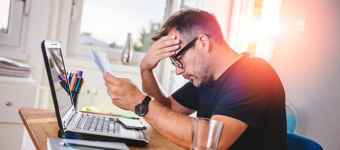 Man with laptop and documents holding head