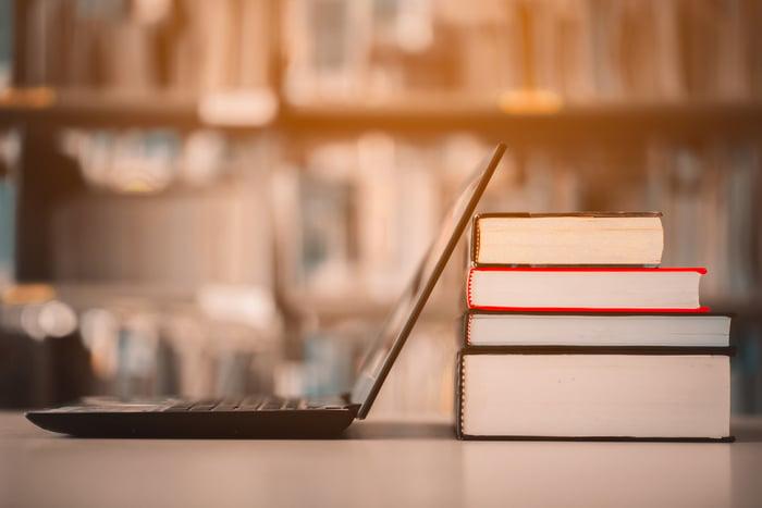 A laptop next to some textbooks