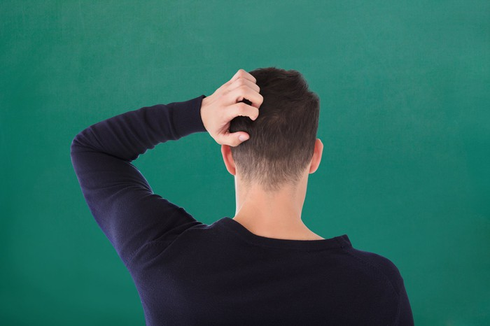 A young businessman stands with his back to the camera, scratching his head.