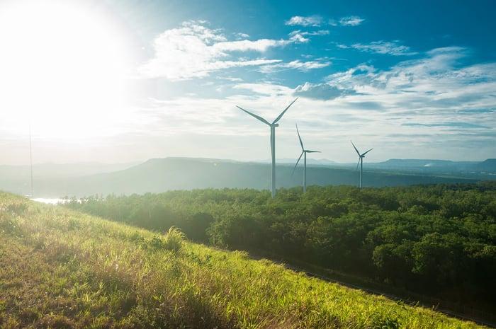 Three wind turbines on a grassy hill at sunrise.