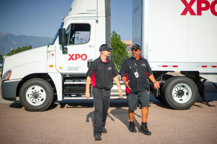 Two XPO Logistics drivers with a company truck in the background.