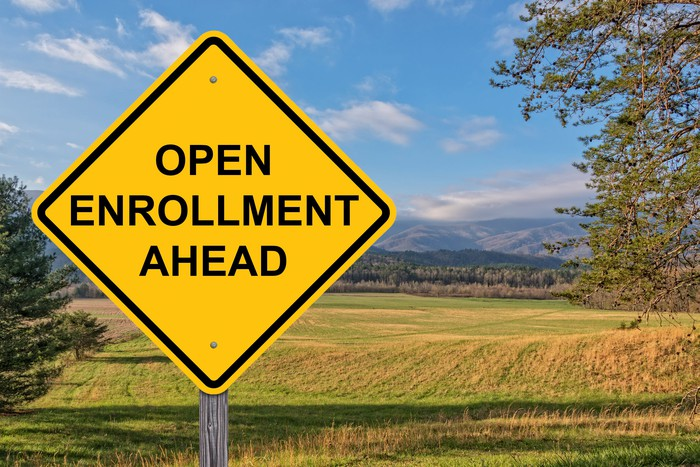 Diamond-shaped road sign in field saying open enrollment ahead