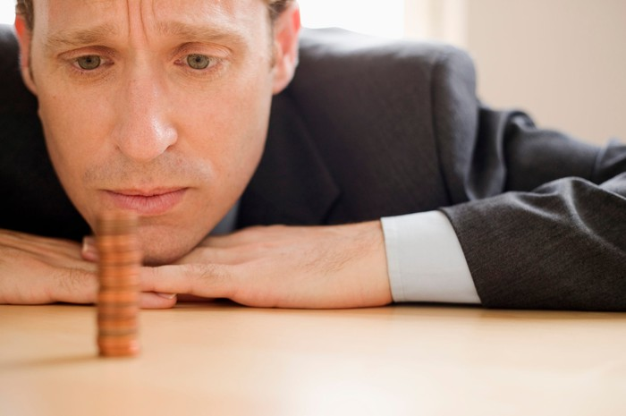 A businessman pensively staring at a neat stack of pennies.