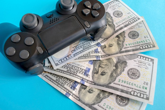 A video game controller on top of four hundred-dollar bills.
