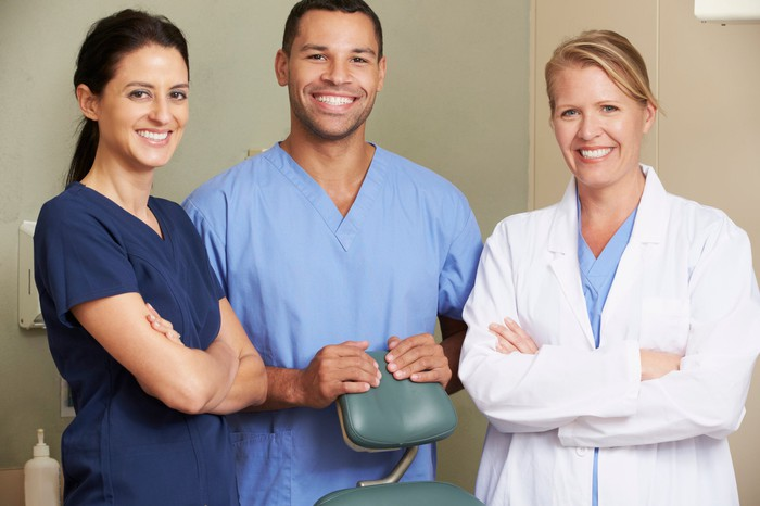 Three smiling healthcare professionals.