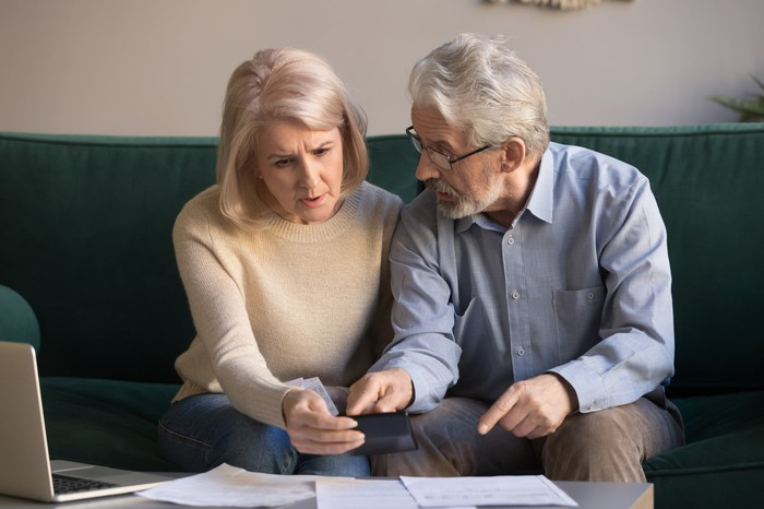 Older man and woman on couch with laptop and documents in front of them
