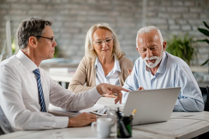 Man pointing to laptop while older man and woman look on