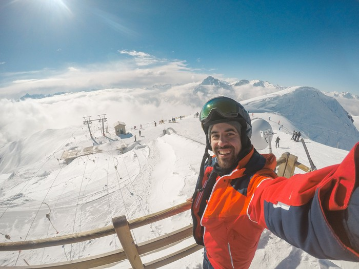 skier holding action camera with slope activity behind him