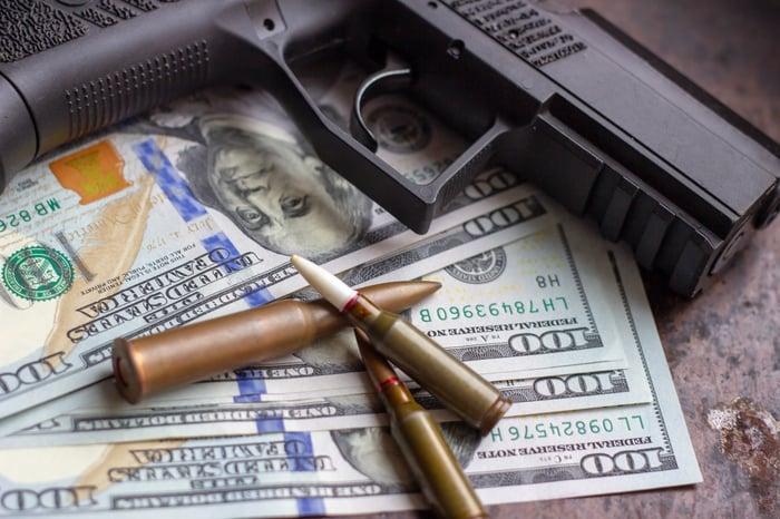 Hand gun and ammo on top of $100 bills representing gun sales.