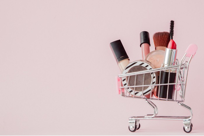 A miniature shopping cart filled with cosmetics.