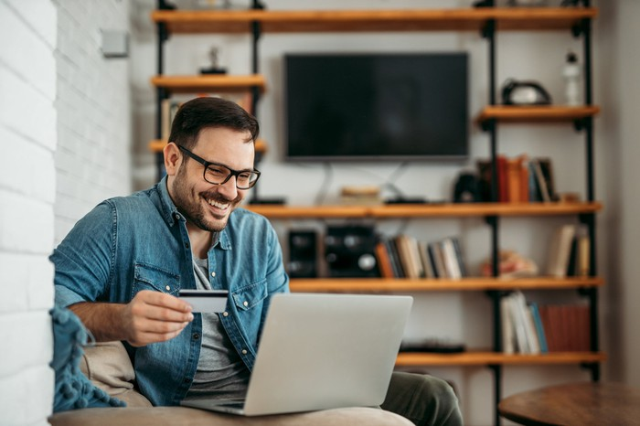 A 30-something man smiles and holds a credit  card while on his laptop in his living room.