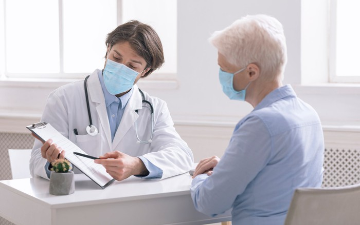 Doctor showing an older patient a report.