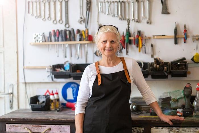 Une personne senior souriante debout devant un poste de travail et des outils.