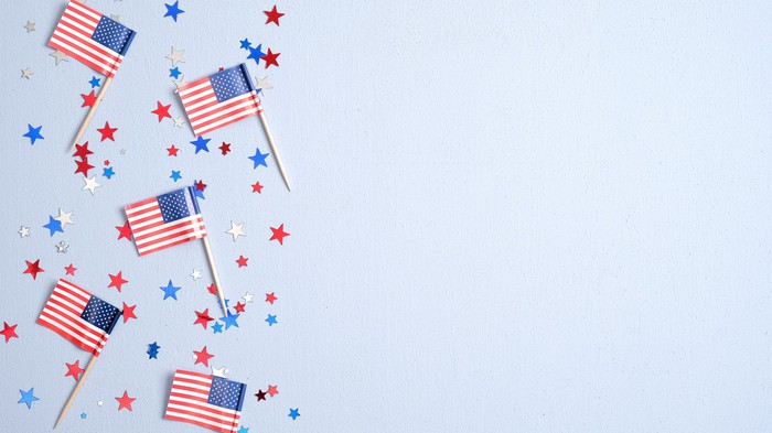 American flags and red white and blue stars on light blue background
