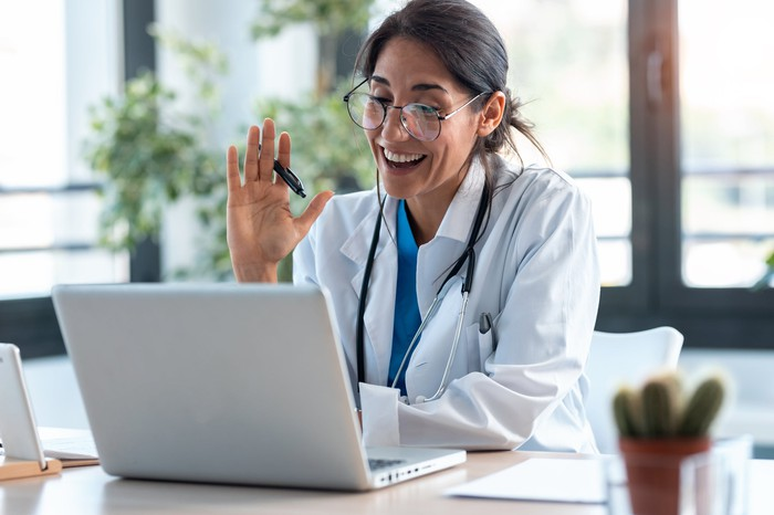 Female doctor wearing glasses, stethoscope, and white lab coat, smiles and waves to a patient during a virtual meeting over the computer.