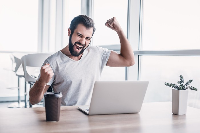 A man celebrating while looking at his laptop computer screen.
