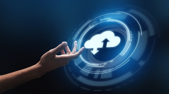 A hand touching an upload-download cloud icon.
