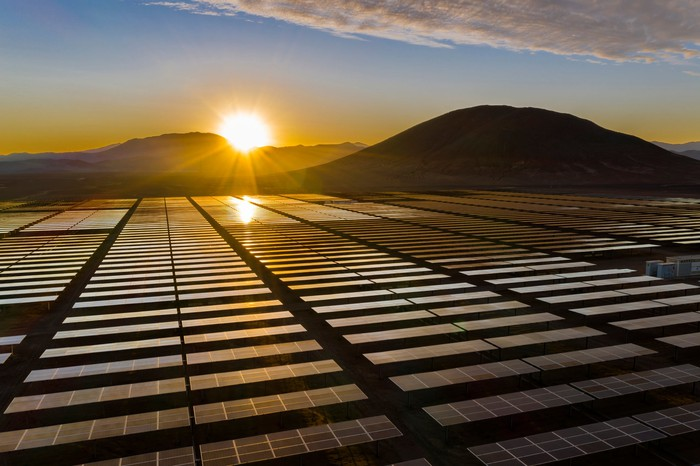 A sun rises over a mountain down on a field of solar panels.