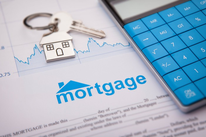 Picture of a mortgage document, house keys, and a calculator