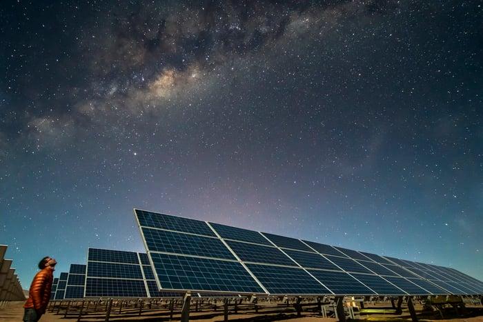 Solar panels under a starry night sky.