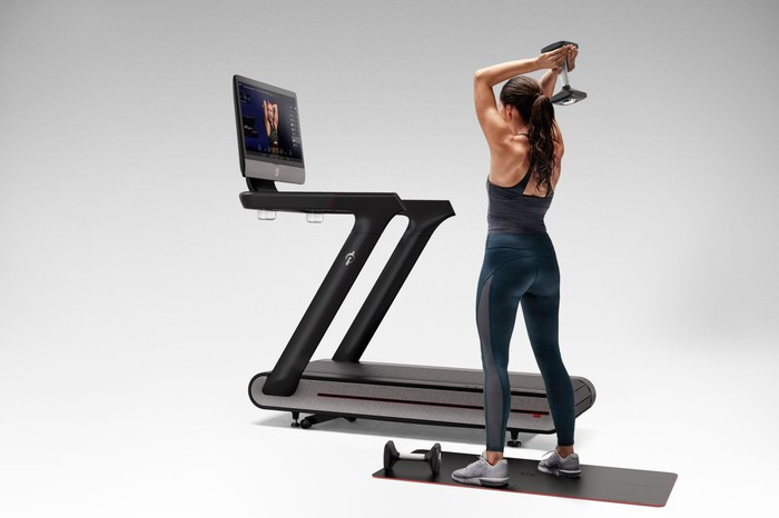 Woman standing next to a Peloton Tread+ and lifting a weight.