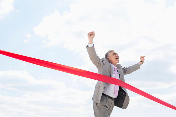 A mature businessman crosses a finish line.