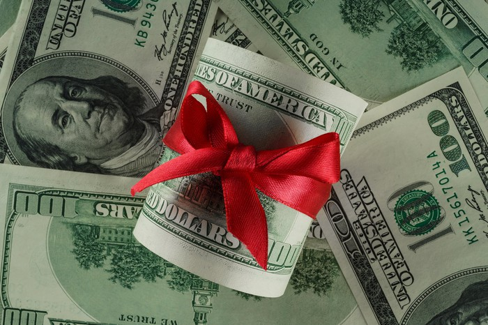A hundred dollar bill wrapped in a gift bow sits on top of a pile of cash.