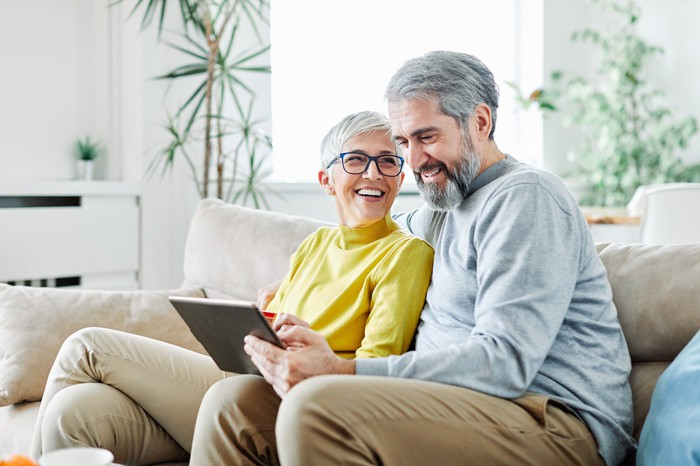 Gray haired couple sit together on a couch looking at a computer and smiling.