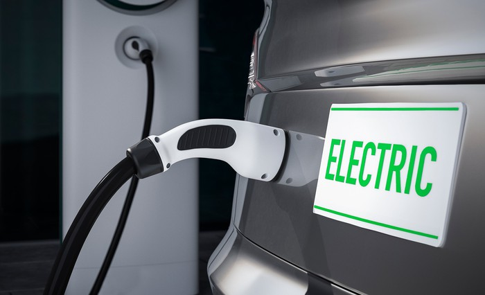 Electric vehicle plugged into outlet.