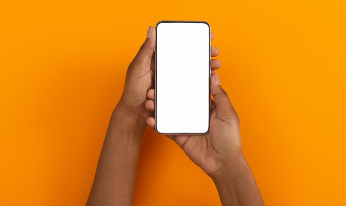 Two hands hold a smartphone with a blank screen.