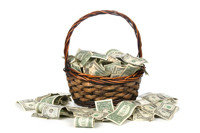 Basket full of cash with cash surrounding it.