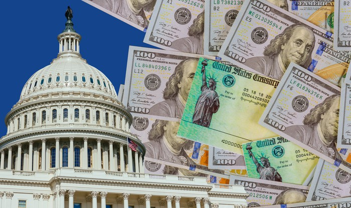 A messy pile of one hundred dollar bills and two stimulus checks next to the Capitol building.