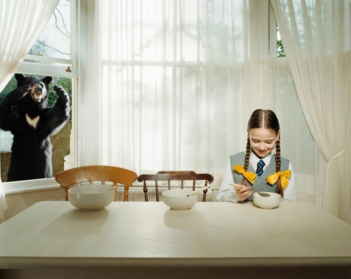 Goldilocks eating porridge while a bear watches.