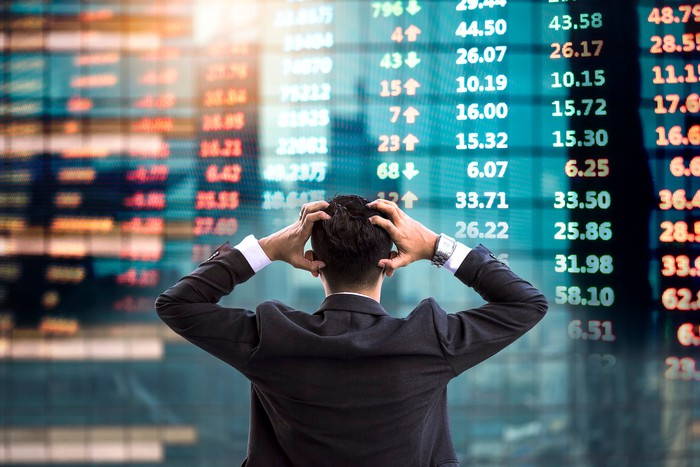 A frustrated businessman watches a wall of stock tickers.