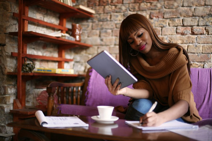 Smiling woman holding tablet and writing in notebook