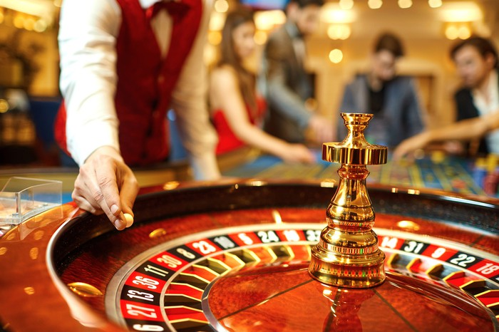 A roulette wheel and dealer on a casino floor