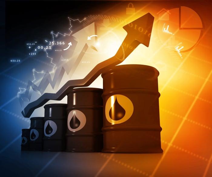 Stock market arrow rising above a stack of oil barrels.