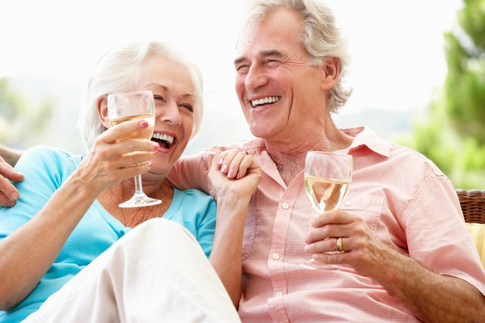 Smiling older man and woman outdoors holding wine glasses
