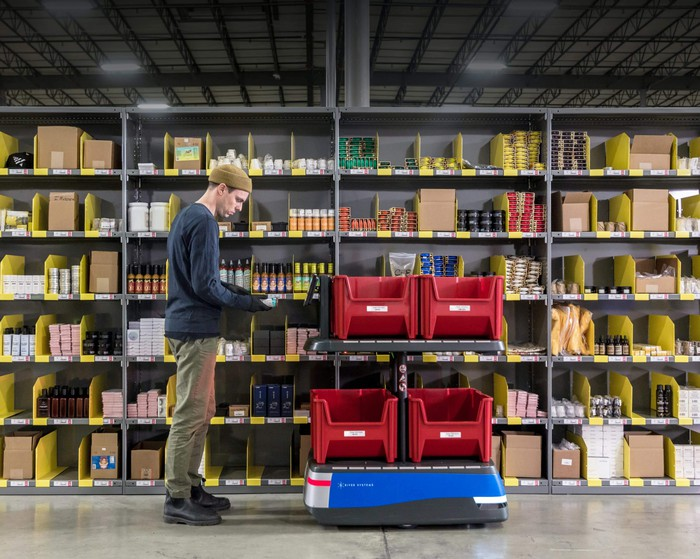 Warehouse employee standing next to shelves of products in bins and a robot with bins to pull products for customer orders.