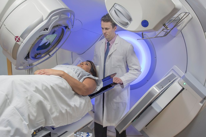 patient and doctor with patient under a cancer scanning machine