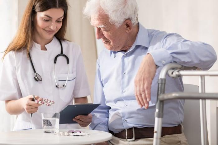 Healthcare professional assisting senior male patient.