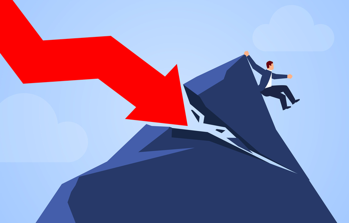 A red charting arrow crashes down on a mountain peak, knocking a businessman down from the top of the mountain.