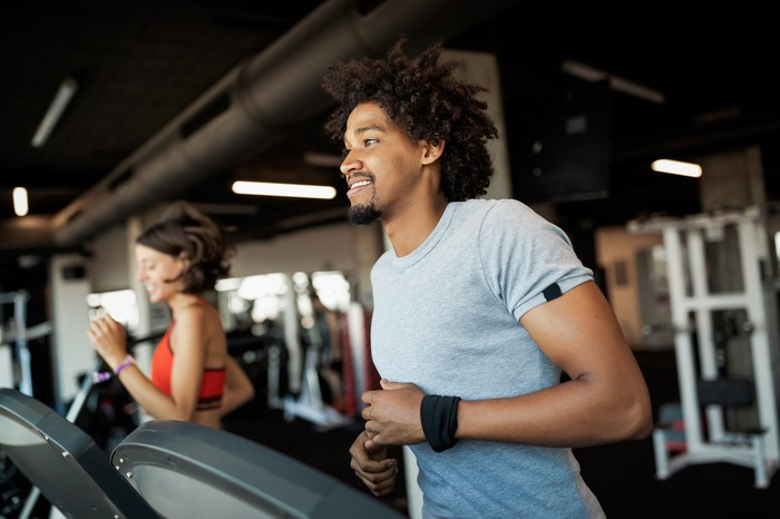 A man and a women running on treadmills in a gym