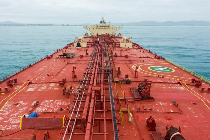 Oil tanker at sea, with coastline ahead.