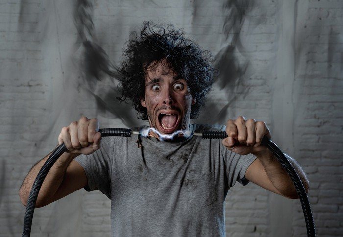 A man covered in soot stares wide-eyed at the electrical charge between the two electrical wires he's holding.