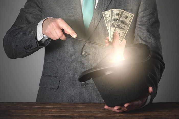 A magician conjures a hand holding several dollar bills from his top hat.