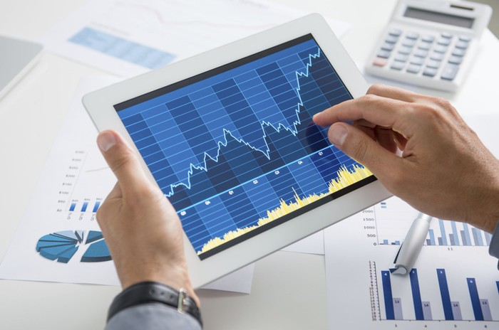 A person holding a tablet that shows a choppy but rising stock chart.
