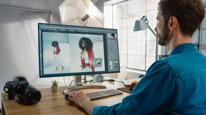 A man uses photo-editing software on a PC.