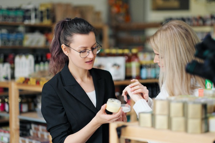 woman working with customer at beauty products area of store