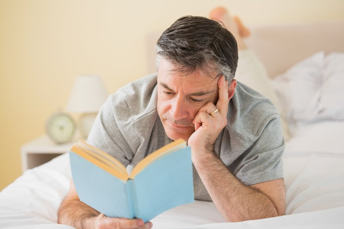Older man lying in bed reading a book